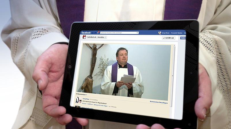 Pfarrer hält Tablet in seinen Händen