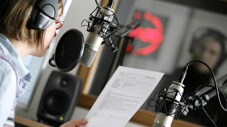Eine junge Frau sitzt im Studio eines Radiosenders und verliest eine Nachricht über das Mikrofon.