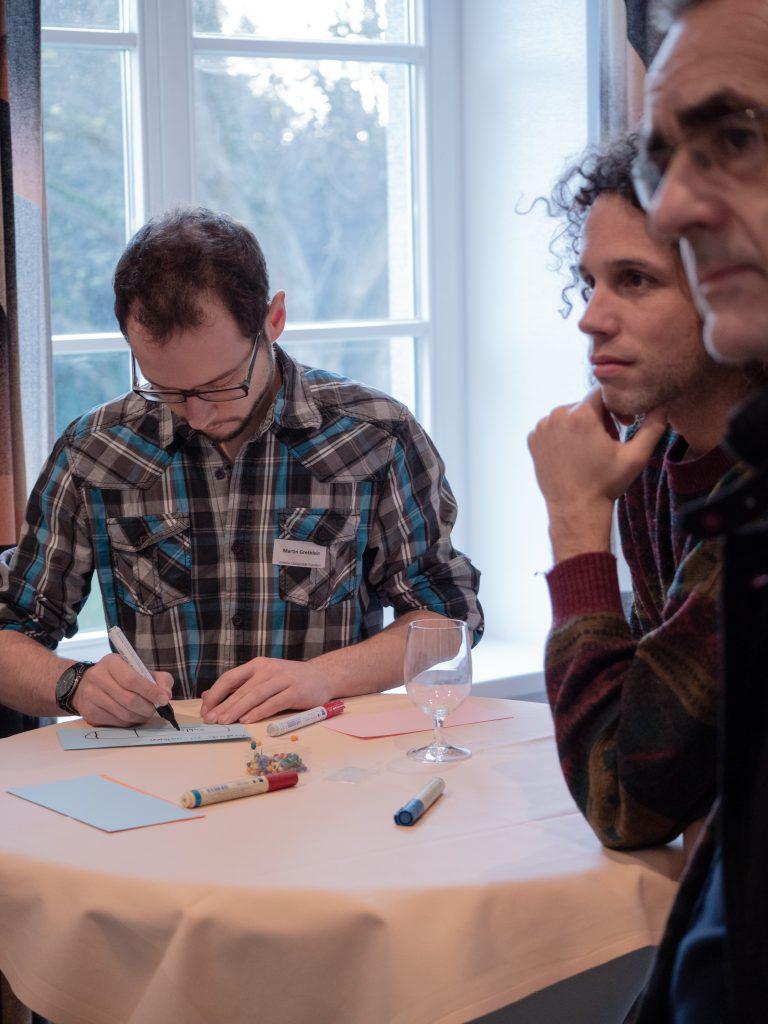 Menschen am Stehtisch im Workshop